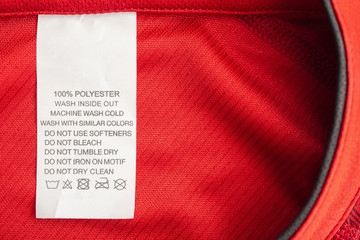 White laundry care washing instructions clothes label on red jersey polyester sport shirt Fototapete