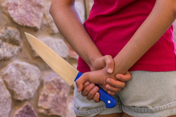 child female violence concept picture of steel kitchen knife in young girl hand behind back