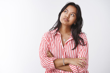 Distressed and pressured young impatient woman staring at upper left corner checking time cross arms over chest and smirking dissatisfied of slow queue, posing against white background