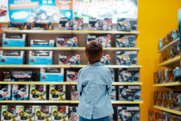 Little boy at the shelf in kids store, back view