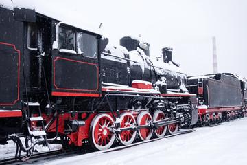 Steam train in snow. Soviet black and red locomotive. Steam engine transport.