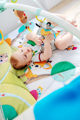 Top view of playful Caucasian chubby six months old baby boy in colorful bodysuit playing with crib toys.
