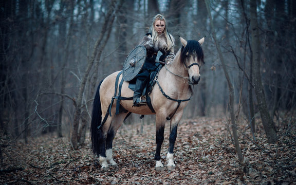 Viking warrior female ridding a horse at twilight autumn forest - Medieval movie scene