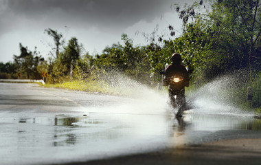Motorcycle run through flood water after hard rain with water spray from the wheels .Stop action (...