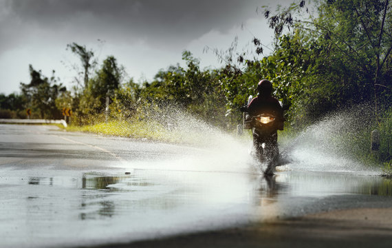 Motorcycle run through flood water after hard rain with water spray from the wheels .Stop action ( capture with the high speed shutter) and selective focus.