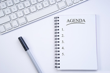 Business agenda, planning concept. Spiral notebook with Agenda text on white background. Flat lay or top view.