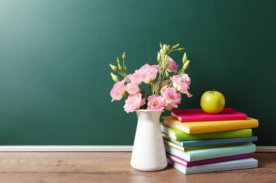 Vase of flowers, books and apple on wooden table near green chalkboard, space for text. Teacher's day