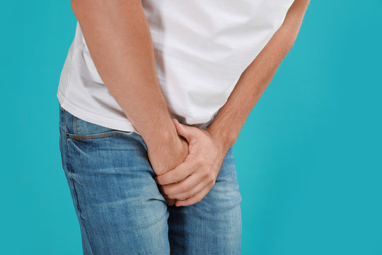 Man suffering from pain on turquoise background, closeup. Urology problems