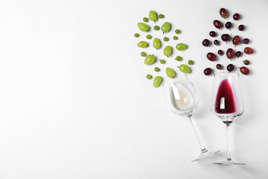 Fresh ripe juicy grapes and glasses of wine on white background, top view