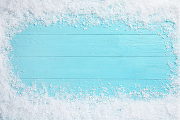 Fotobehang - Frame of white snow on light blue wooden background, top view with space for text. Christmas season