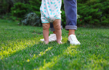 Cute little baby learning to walk with his nanny on green grass outdoors, closeup Fototapete