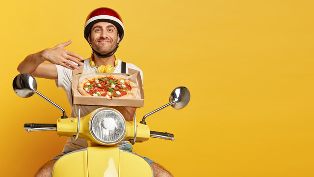 Mmm, how delicious! Satisfied man enjoys pleasant smell from freshly baked pizza on cardboard box, has good appetite, transports delicious snack for clients, poses over yellow scooter in helmet