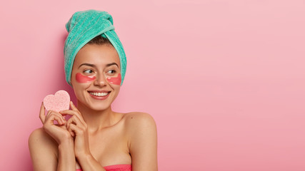 Portrait of lovely young woman uses eye patches for skin treatment, looks healthy and pleased, holds little cosmetic sponge for removing makeup, looks aside right with thoughtful happy expression
