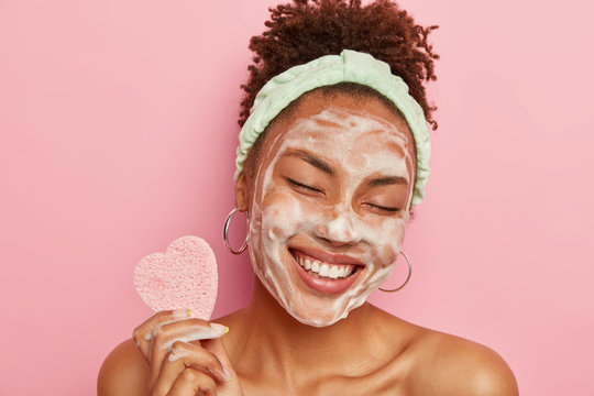 Beautiful optimistic Afro American woman cleanses face with foam, refreshes skin, has well cared complexion, holds heart shaped sponge for beauty procedures, stands bare shoulders with closed eyes