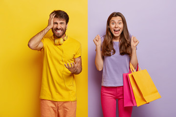 Cheerful female carries colorful shopping bags, rejoices new purchase, clenches fists with joy, annoyed husband feels angry with wife shopaholic, gestures with irritation, poses against colorful wall