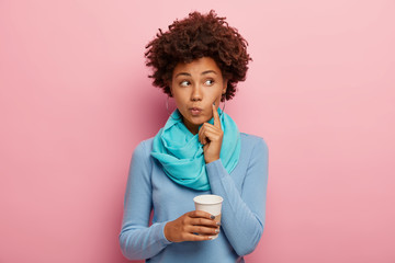 Afro American curly woman keeps index finger on cheek, looks thoughtfully aside, contemplates about something with hot drink, holds paper cup, wears blue jumper, has coffee break isolated on pink wall