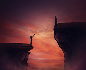 Two persons standing on different high peaks showing the divergence of success achievement. Inequality between people concept as global social issue. Discrimination, injustice and unfairness symbol.