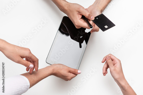 Close up top view of a woman hands over bank card to a man