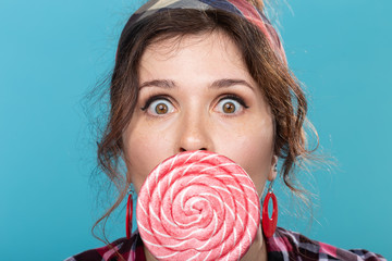 candy, diet and junk food concept - portrait of surprised pin-up woman with big lollipop on blue background