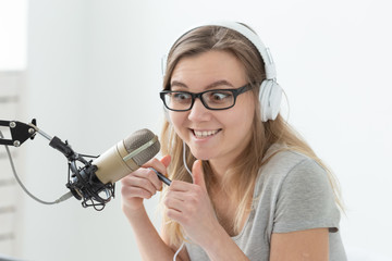 Radio host concept - Funny woman working as radio host sitting in front of microphone over white background in studio