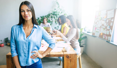 Attractive confident modern business woman in casual clothes looks at the camera and smiling. Modern start-up business team. Co-workers or students