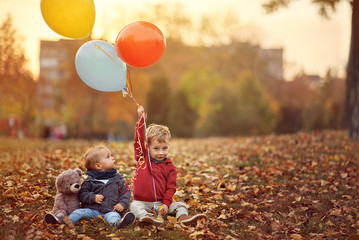 boys playing with balloons in the autumn park.