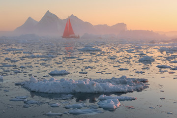 Red sailing boat among icebergs at sunset
