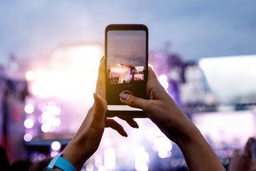 A girl is taking pictures of a street concert on the phone.