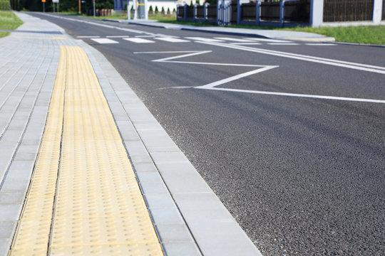 Droga asfaltowa, chodnik, przejście dla pieszych w obszarze zabudowanym.