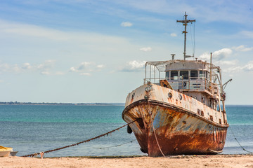 In de dag Schip An old weathered and rusting ship/fishing boat anchored on the beach of the Island of Mozambique (Ilha de Mocambique) on a sunny day. Nampula Province, Mozambique, Africa