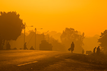 The silhouettes of Mozambican commuters  along a tarmac road at sunrise, making their way into Nampula Town. Mozambique
