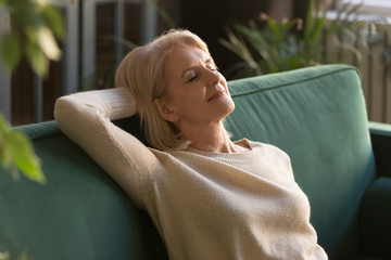 Exhausted mature woman relax on couch with eyes closed