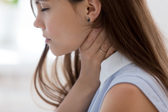 Unwell young woman touch neck suffering from angina