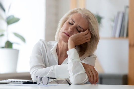 Exhausted senior businesswoman fall asleep at workplace