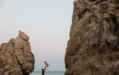 A man plays with his child at Petra tou Romiou (Romios' stone) beach, which according to the myth it is the birthplace of Aphrodite, the Greek goddess of love and beauty