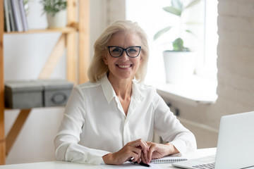 Portrait of smiling senior businesswoman posing at workplace