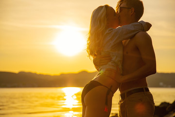 Young Man Kissing Girlfriend Standing At Beach In Beautiful Sunset