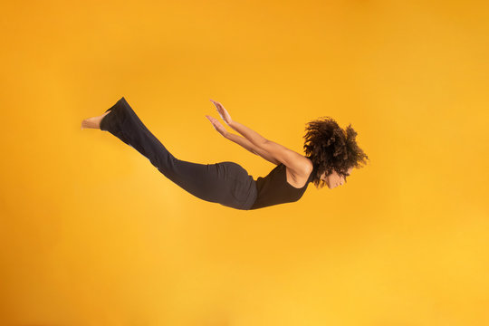 Side view of afro hair woman in zero gravity or a fall. Girl is flying, falling or floating in the air. Side view of person. Over yellow background. Girl flies down jumping from a helicopter.
