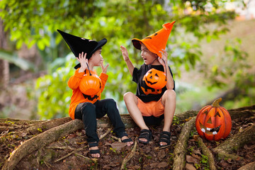 Asian kids with pumpkins in Halloween costumes.