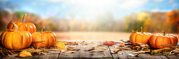 Thanksgiving Pumpkins And Leaves On Rustic Wooden Table With Sunlight And Bokeh On Autumn...