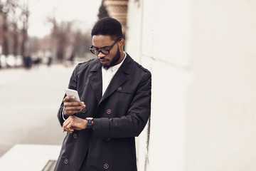 Afro businessman checking time on watches and using phone
