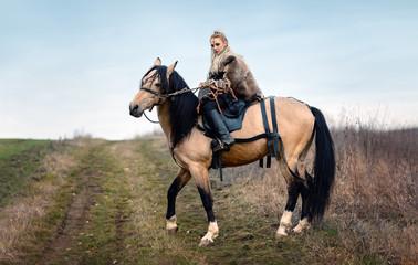 Warrior viking blonde female riding a horse - Medieval movie scene
