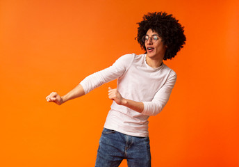 Cheerful bushy black man dancing on orange background