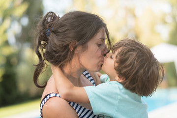 Mother kissing son in garden outdoors images