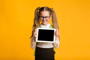 School Girl Showing Empty Tablet Screen, Yellow Background, Mockup