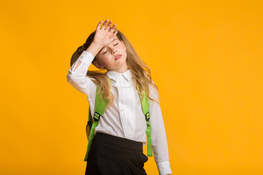 Little Schoolgirl Feeling Bad Touching Head, Yellow Background