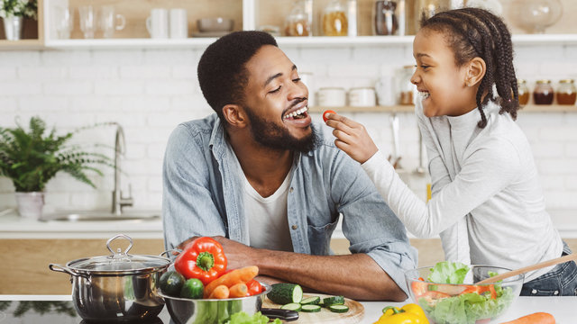 Cute african girl giving her dad cherry tomato while cooking