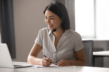 Happy asian woman wearing headset, helping client with problem.