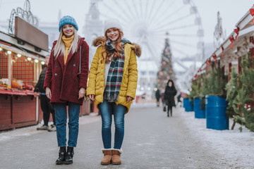 Fototapete - Friendly girls standing in the middle of festive market