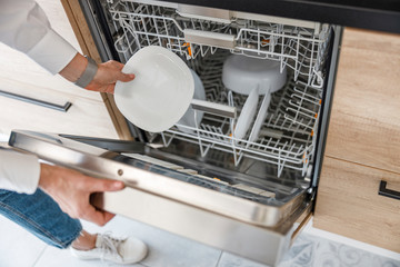 Woman taking a plate from the dishwasher